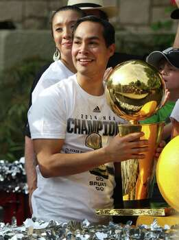 Mayor Julian Castro holds onto one of the five O'Brien Trophies while taking part in the river parade with his wife, Erica, for the San Antonio Spurs after the team capture their fifth NBA championship on Wednesday, June 18, 2014. Photo: Kin Man Hui, San Antonio Express-News / ©2014 San Antonio Express-News