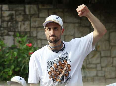 San Antonio Spurs' Manu Ginobili gestures to the crowd during the river parade for the San Antonio Spurs after the team capture their fifth NBA championship on Wednesday, June 18, 2014. Photo: Kin Man Hui, San Antonio Express-News / ©2014 San Antonio Express-News