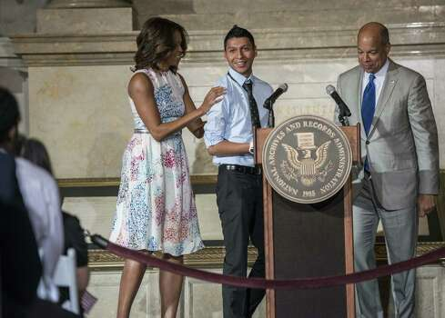 First lady Michelle Obama and Secretary of Homeland Security Jeh Johnson stand with newly sworn in citizen Juan Cue Monroy during a naturalization ceremony Wednesday  in the nation's capital. Photo: Brendan Smialowski / Getty Images / AFP