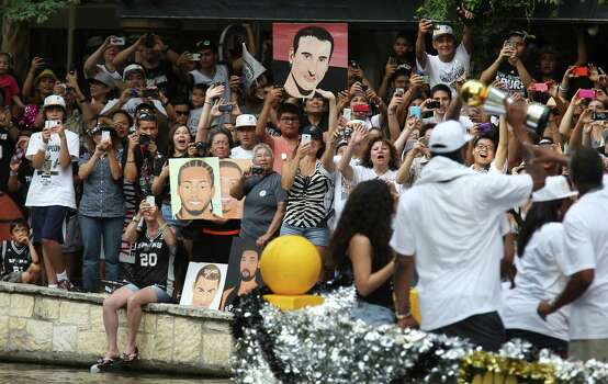 Fans line the San Antonio River during a parade for the San Antonio Spurs after the team capture their fifth NBA championship on Wednesday, June 18, 2014. Photo: Kin Man Hui, San Antonio Express-News / ©2014 San Antonio Express-News