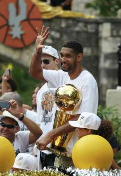 San Antonio Spurs' Tim Duncan waves to the crowd at the Arneson Theater while holding one of the five O'Brien Trophies during the river parade for the Spurs after the team capture their fifth NBA championship on Wednesday, June 18, 2014. Photo: Kin Man Hui, San Antonio Express-News / ©2014 San Antonio Express-News