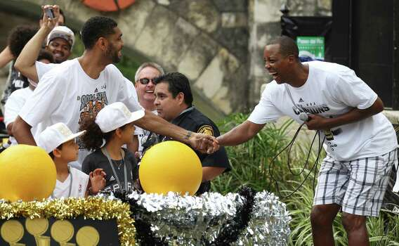 San Antonio Spurs' Tim Duncan (left) playfully attempts to pull former teammate Sean Elliott in the San Antonio River during a parade for the Spurs after the team capture their fifth NBA championship on Wednesday, June 18, 2014. Photo: Kin Man Hui, San Antonio Express-News / ©2014 San Antonio Express-News