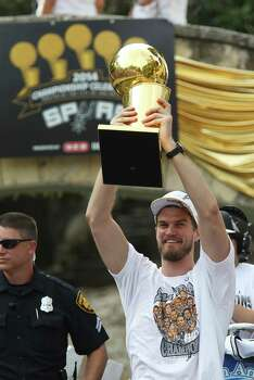San Antonio Spurs' Tiago Splitter holds up the O'Brien Trophy during the river parade for the San Antonio Spurs after the team capture their fifth NBA championship on Wednesday, June 18, 2014. Photo: Kin Man Hui, San Antonio Express-News / ©2014 San Antonio Express-News