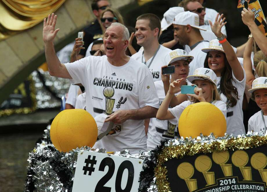 San Antonio Spurs head coach Gregg Popovich waves to the crowd during the river parade for the Spurs after the team capture their fifth NBA championship on Wednesday, June 18, 2014. Photo: Kin Man Hui, San Antonio Express-News / ©2014 San Antonio Express-News