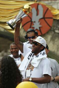 San Antonio Spurs' Kawhi Leonard hoists up the MVP Trophy during the river parade for the San Antonio Spurs after the team capture their fifth NBA championship on Wednesday, June 18, 2014. Photo: Kin Man Hui, San Antonio Express-News / ©2014 San Antonio Express-News