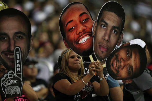 San Antonio Spurs fans hold cutouts of Manu Ginobili, Kawhi Leonard, Danny Green and Tim Duncan as they gather at the Alamodome for the Championship Celebration, Wednesday, June 18, 2014. Photo: Jerry Lara, San Antonio Express-News / ©2014 San Antonio Express-News