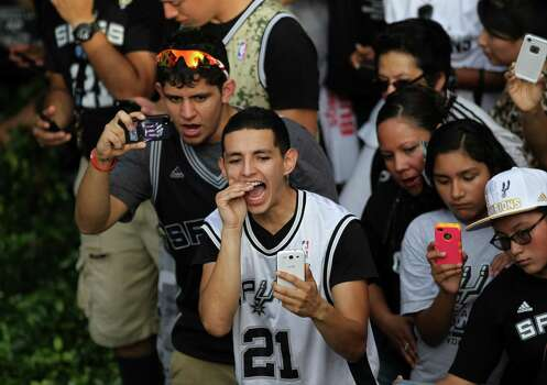 Spurs fans cheer along the San Antonio River during the river parade on Wednesday, June 18, 2014. Photo: Timothy Tai, San Antonio Express-News / © 2014 San Antonio Express-News