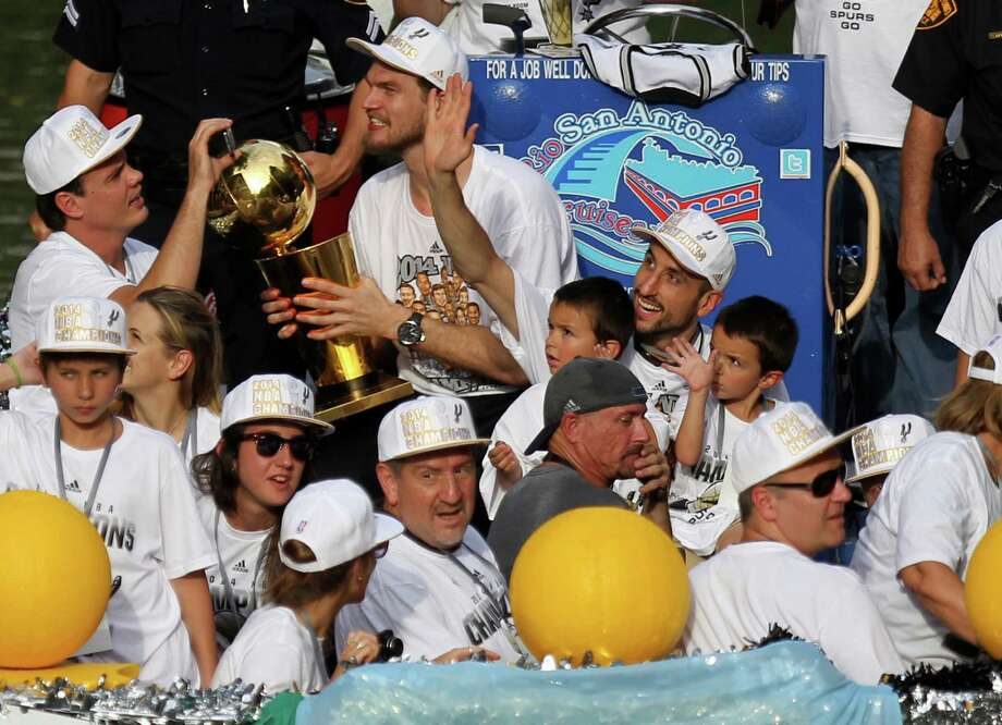 San Antonio Spurs' Tiago Splitter holds the O'Brien Trophy as Manu Ginobili waves with his twin sons during the river parade on Wednesday, June 18, 2014, on the San Antonio River. Photo: Timothy Tai, San Antonio Express-News / © 2014 San Antonio Express-News