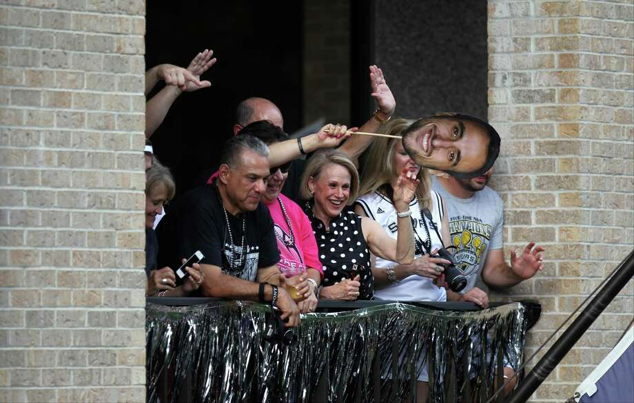 Spurs fans cheer from the Greater San Antonio Chamber of Commerce building along the San Antonio River during the river parade on Wednesday, June 18, 2014. Photo: Timothy Tai, San Antonio Express-News / © 2014 San Antonio Express-News