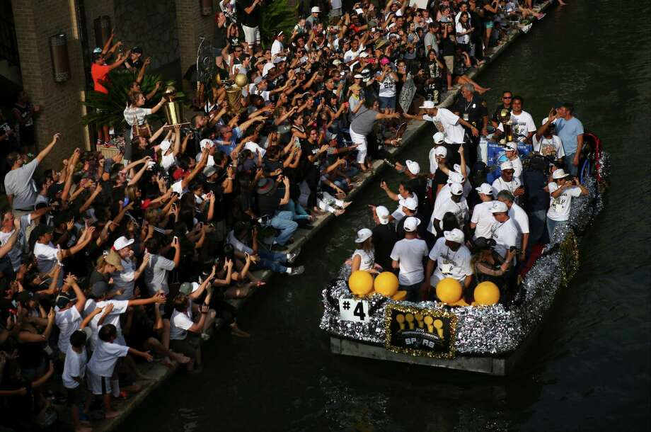 San Antonio Spurs' Tony Parker reaches from a float to a fan along the San Antonio River during the river parade on Wednesday, June 18, 2014. Photo: Timothy Tai, San Antonio Express-News / © 2014 San Antonio Express-News
