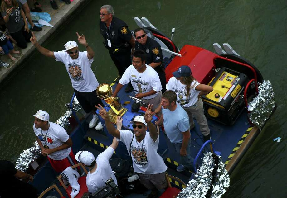 San Antonio Spurs' Boris Diaw, bottom center, and Tony Parker, top left, wave to the crowd during the river parade on Wednesday, June 18, 2014, on the San Antonio River. Photo: Timothy Tai, San Antonio Express-News / © 2014 San Antonio Express-News