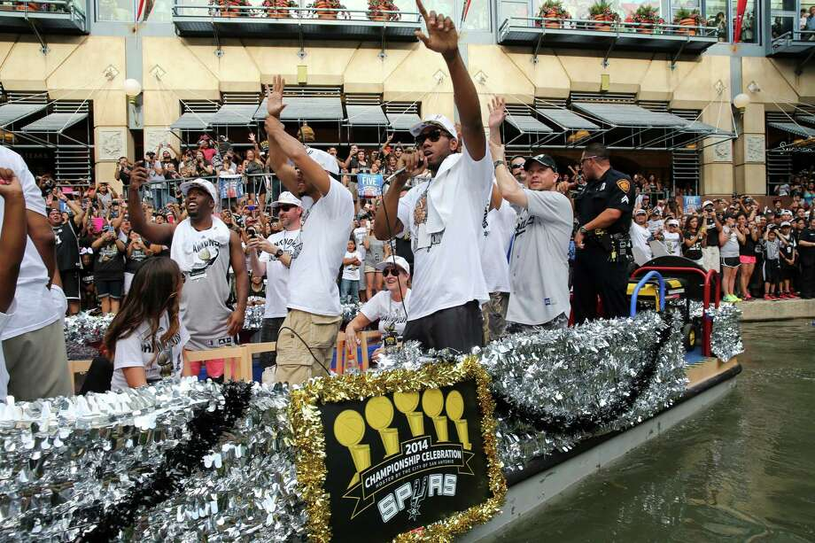 San Antonio Spurs' Kawhi Leonard (center) gestures Wednesday June 18, 2014 during the river parade for the San Antonio Spurs after the team captured their fifth NBA championship. Photo: Edward A. Ornelas, San Antonio Express-News / © 2014 San Antonio Express-News
