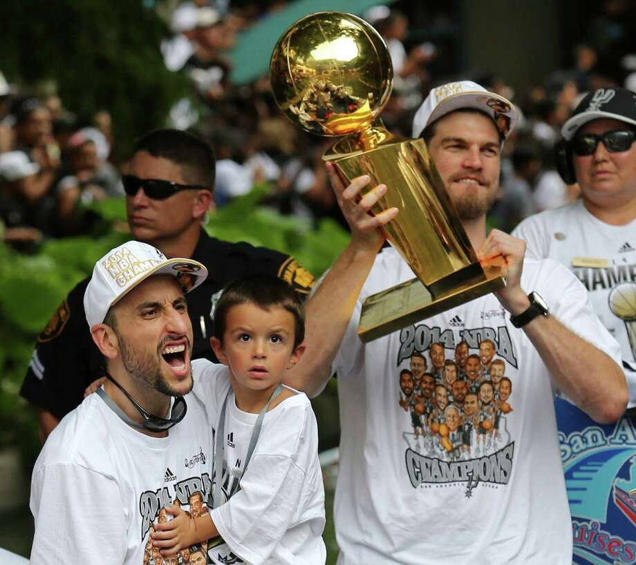 San Antonio Spurs' Manu Ginobili yells while holding one of his twin sons as teammate Tiago Splitter holds the O'Brien Trophy Wednesday June 18, 2014 during the river parade for the San Antonio Spurs after the team captured their fifth NBA championship. Photo: Edward A. Ornelas, San Antonio Express-News / © 2014 San Antonio Express-News