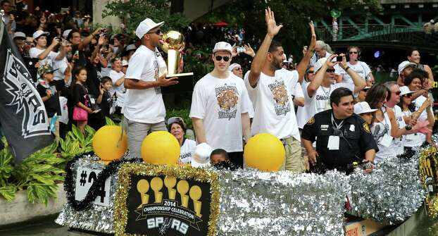 San Antonio Spurs' Patty Mills (from left), Aron Baynes, and Tim Duncan react Wednesday June 18, 2014 during the river parade for the San Antonio Spurs after the team captured their fifth NBA championship. Photo: Edward A. Ornelas, San Antonio Express-News / © 2014 San Antonio Express-News