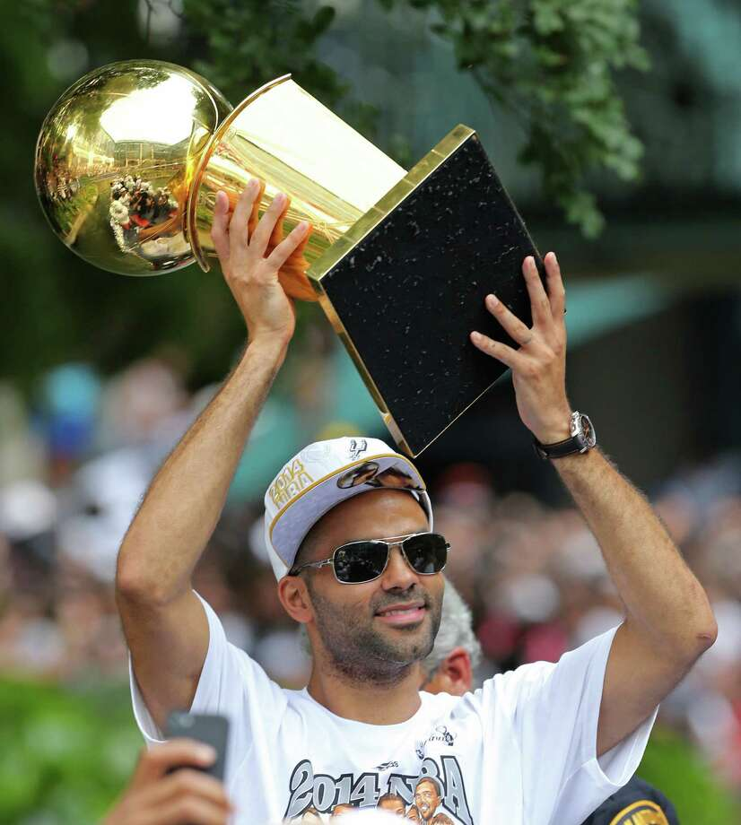San Antonio Spurs' Tony Parker holds the O'Brien Trophy Wednesday June 18, 2014 during the river parade for the San Antonio Spurs after the team captured their fifth NBA championship. Photo: Edward A. Ornelas, San Antonio Express-News / © 2014 San Antonio Express-News