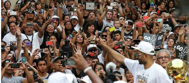 San Antonio Spurs fans photograph Tony Parker as he passes with the O'Brien Trophy Wednesday June 18, 2014 during the river parade for the San Antonio Spurs after the team captured their fifth NBA championship. Photo: Edward A. Ornelas, San Antonio Express-News / © 2014 San Antonio Express-News