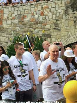 Gregg Popovich waves to the crowd along the River Walk during the Spurs river parade on Wednesday, June 18, 2014. Photo: Mitchell Ferman / San Antonio Express-News