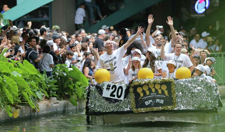 San Antonio Spurs head coach Gregg Popovich (left) and others wave Wednesday June 18, 2014 during the river parade for the San Antonio Spurs after the team captured their fifth NBA championship. Photo: Edward A. Ornelas, San Antonio Express-News / © 2014 San Antonio Express-News