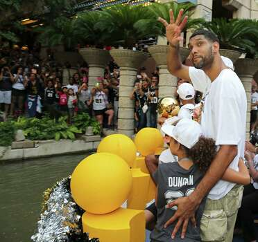 San Antonio Spurs' Tim Duncan waves as he hugs his daughter Sydney Wednesday June 18, 2014 during the river parade for the San Antonio Spurs after the team captured their fifth NBA championship. Photo: Edward A. Ornelas, San Antonio Express-News / © 2014 San Antonio Express-News