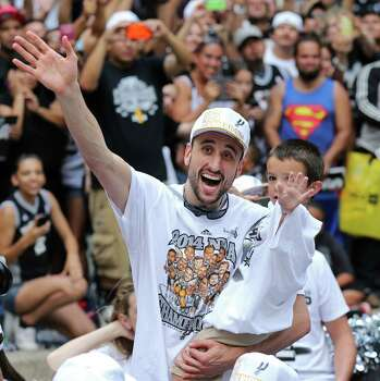 San Antonio Spurs' Manu Ginobili waves while holding one of his twin sons Wednesday June 18, 2014 during the river parade for the San Antonio Spurs after the team captured their fifth NBA championship. Photo: Edward A. Ornelas, San Antonio Express-News / © 2014 San Antonio Express-News
