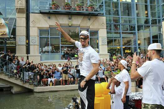 San Antonio Spurs' Danny Green (left) waves to fans Wednesday June 18, 2014 during the river parade for the San Antonio Spurs after the team captured their fifth NBA championship. Photo: Edward A. Ornelas, San Antonio Express-News / © 2014 San Antonio Express-News
