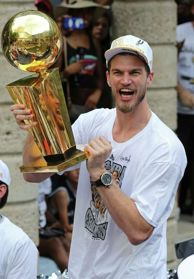 San Antonio Spurs' Tiago Splitter holds the O'Brien Trophy Wednesday June 18, 2014 during the river parade for the San Antonio Spurs after the team captured their fifth NBA championship. Photo: Edward A. Ornelas, San Antonio Express-News / © 2014 San Antonio Express-News