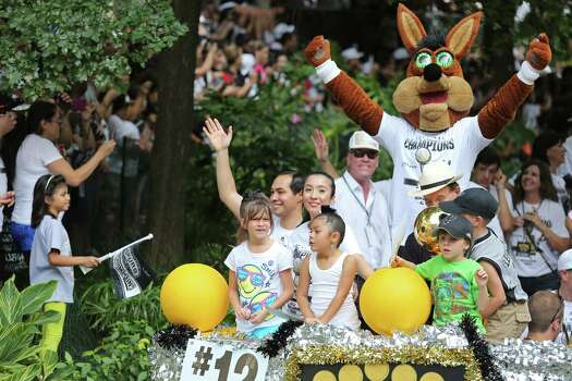 Mayor Julian Castro (second from left) his wife Erica, daughter Carina, the Spurs Coyote and others take part in the river parade for the San Antonio Spurs, Wednesday June 18, 2014, after the team captured their fifth NBA championship. Photo: Edward A. Ornelas, San Antonio Express-News / © 2014 San Antonio Express-News