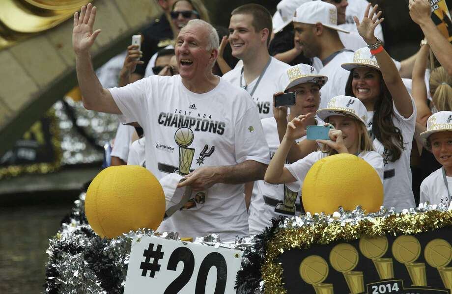 A smiling Gregg Popovich positively beams while waving to the crowd that gathered to celebrate his team's fifth National Basketball Association championship. Photo: Kin Man Hui / San Antonio Express-News / ©2014 San Antonio Express-News