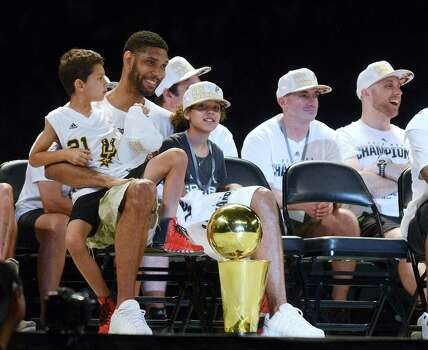 Tim Duncan sits with his children, Sydney and Draven, onstage during a celebration of the Spurs fifth NBA championship on Wednesday, June 18, 2014, in the Alamodome. Photo: Billy Calzada, San Antonio Express-News / San Antonio Express-News