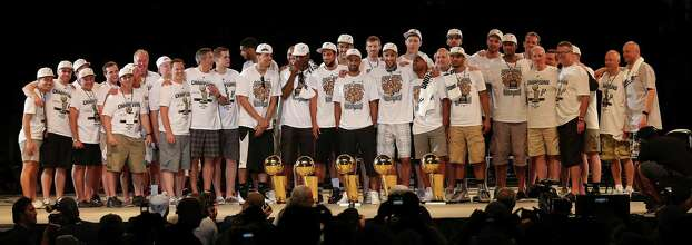 The San Antonio Spurs pose with the trophies toward the end of the Championship Celebration at the Alamodome, Wednesday, June 18, 2014. The Spurs beat the Miami Heat in the NBA Finals on Sunday to claim the title. The celebration started with a river parade and ended at the Alamodome. Photo: Jerry Lara, San Antonio Express-News / ©2014 San Antonio Express-News