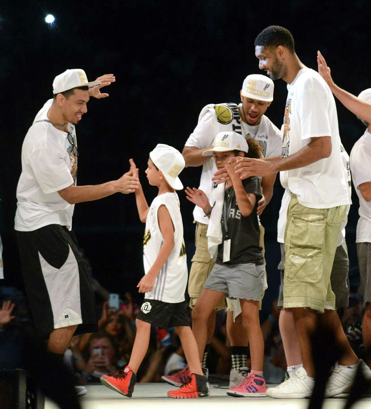 Spurs player Danny Green, left, greets Tim Duncan and his children, Draven and Sydney, during a celebration of the Spurs fifth NBA championship on Wednesday, June 18, 2014, in the Alamodome.