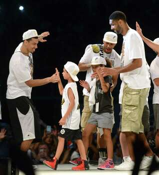 Spurs player Danny Green, left, greets Tim Duncan and his children, Draven and Sydney, during a celebration of the Spurs fifth NBA championship on Wednesday, June 18, 2014, in the Alamodome. Photo: Billy Calzada, San Antonio Express-News / San Antonio Express-News