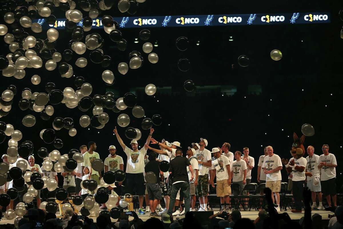 Balloons rain down on the San Antonio Spurs after a team picture with the trophies at the Championship Celebration at the Alamodome, Wednesday, June 18, 2014. The Spurs beat the Miami Heat in the NBA Finals on Sunday to claim the title. The celebration started with a river parade and ended at the Alamodome.