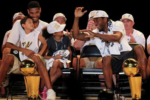 San Antonio Spurs Tim Duncan reaches over to tease Kawhi Leonard during the Championship Celebration at the Alamodome, Wednesday, June 18, 2014. The Spurs beat the Miami Heat in the NBA Finals on Sunday to claim the title. The celebration started with a river parade and ended at the Alamodome. With Duncan are his children, Draven, left, and Sydney. Photo: Jerry Lara, San Antonio Express-News / ©2014 San Antonio Express-News