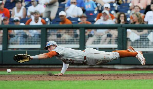 Texas first baseman Kacy Clemens (42) attempts to catch the ball hit for a single by UC Irvine's Kris Paulino in the second inning of an NCAA baseball College World Series elimination game in Omaha, Neb., Wednesday, June 18, 2014. (AP Photo/Eric Francis) Photo: Eric Francis, Associated Press / FR9944 AP