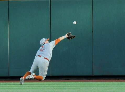 Texas center fielder Mark Payton (2) makes a leaping catch of a fly ball hit by UC Irvine's Taylor Sparks in the third inning of an NCAA baseball College World Series elimination game in Omaha, Neb., Wednesday, June 18, 2014. (AP Photo/Eric Francis) Photo: Eric Francis, Associated Press / FR9944 AP