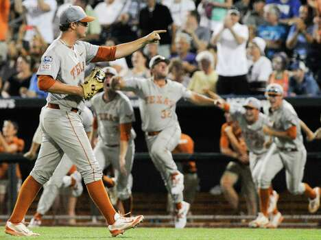 Texas pitcher Travis Duke points as texas players erupt from the dugout after the last out against UC Irvine, in an NCAA baseball College World Series elimination game in Omaha, Neb., Wednesday, June 18, 2014. Texas beat UC Irvine 1-0. (AP Photo/Eric Francis) Photo: Eric Francis, Associated Press / FR9944 AP