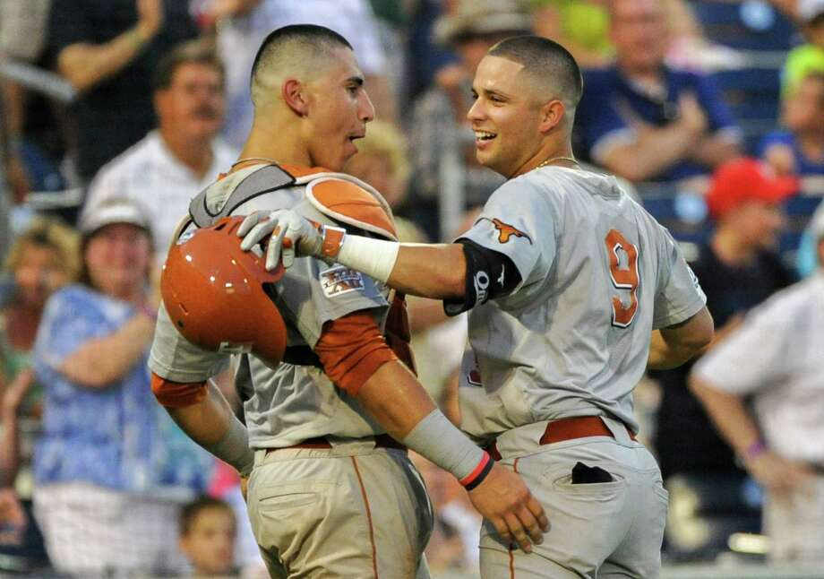 Texas' C.J Hinojosa (9) celebrates with Texas catcher Tres Barrera (1) after Hinojosa hit a solo home run in the seventh inning of an NCAA baseball College World Series elimination game against UC Irvine in Omaha, Neb., Wednesday, June 18, 2014. (AP Photo/Ted Kirk) Photo: Ted Kirk, Associated Press / FR34398 AP