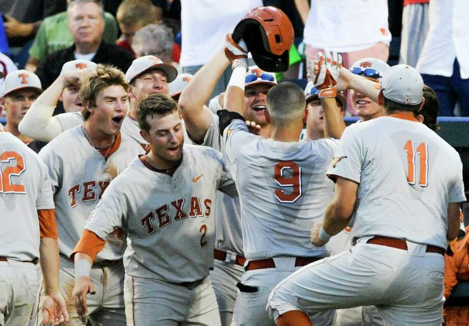 Texas players greet C.J Hinojosa (9) to the dugout after he hit a home run against UC Irvine in the seventh inning of an NCAA baseball College World Series elimination game in Omaha, Neb., Wednesday, June 18, 2014. (AP Photo/Eric Francis) Photo: Eric Francis, Associated Press / FR9944 AP