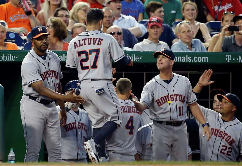 After singing the praises of Jose Altuve (27) before the game, manager Bo Porter, left, greets Altuve after he scored in the fourth inning. Altuve began the inning with a walk and also had two hits Wednesday to raise his average to .329. Photo: Alex Brandon, STF / AP