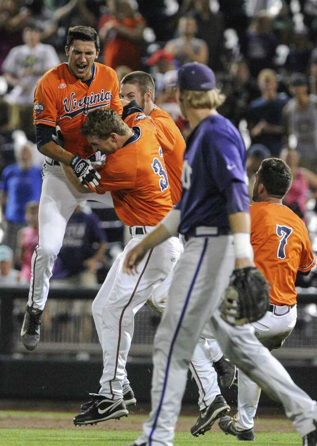 Virginia players celebrate after scoring in the 15th inning to defeat TCU late Tuesday in Omaha. The Horned Frogs face Mississippi in an elimination game today. Photo: Eric Francis / Associated Press / FR9944 AP