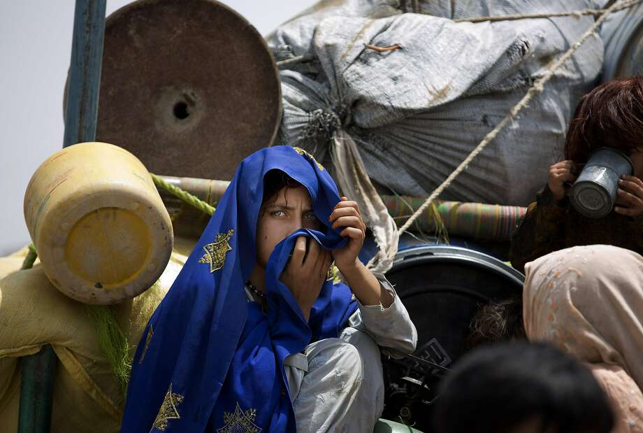 A Pakistani tribal girl sits next to her belongings on a truck after arriving to Bannu, Pakistan, Wednesday, June 18, 2014. Thousands of villagers fled as Pakistani army relax a curfew in troubled North Waziristan. Pakistani jets pounded targets in the country's northwest in major offensives  designed to root out safe havens in the volatile region. (AP Photo/B.K. Bangash) Photo: B.K. Bangash, Associated Press