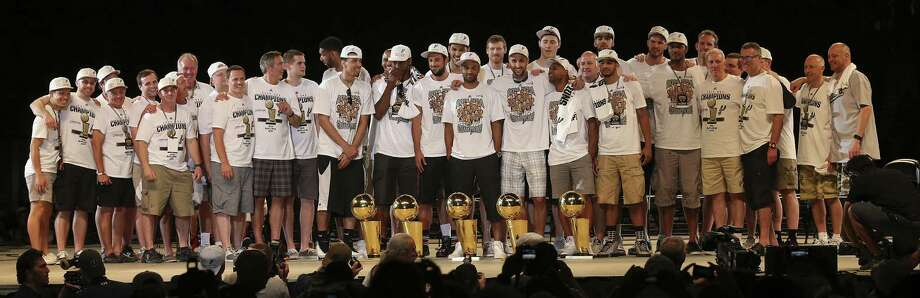 To the delight of the cheering thousands who assembled for the celebration in the Alamodome, the players and others involved in the Spurs' championship 2013-14 season display the team's five National Basketball Association trophies, which date to 1999. The latest trophy provided redemption for the Spurs' loss to the Heat last year. Photo: Jerry Lara / San Antonio Express-News / ©2014 San Antonio Express-News