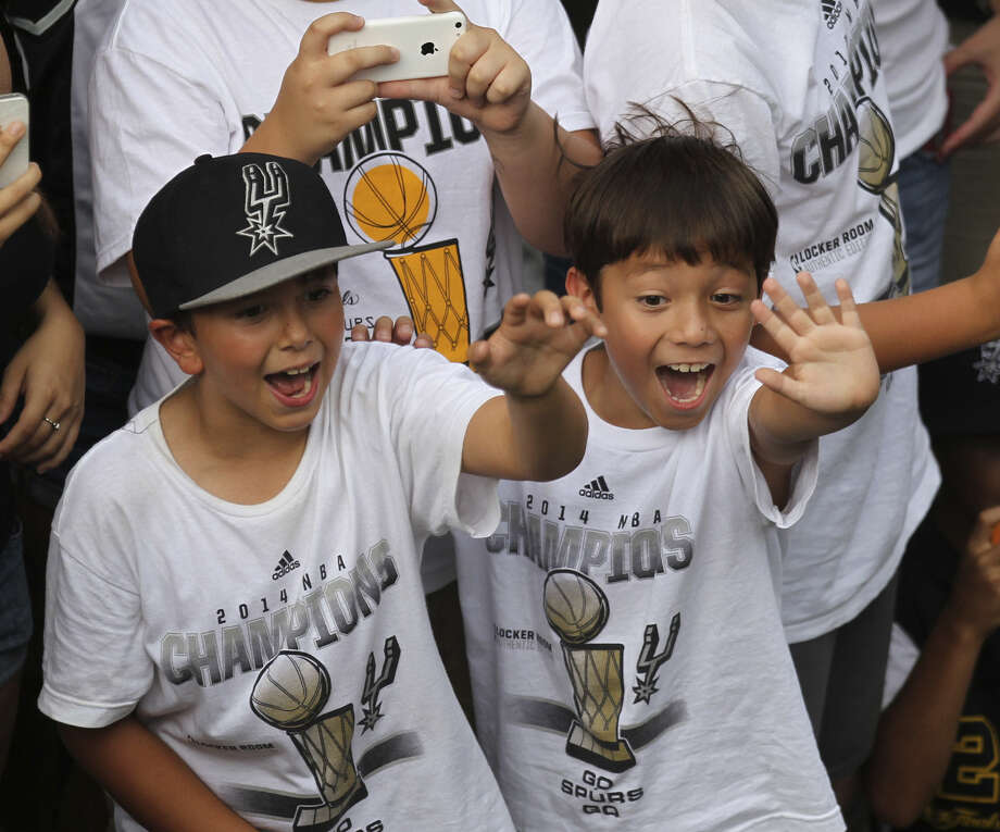 Young fans are caught up in the excitement as the river parade passes their vantage point. Photo: Timothy Tai / San Antonio Express-News / © 2014 San Antonio Express-News