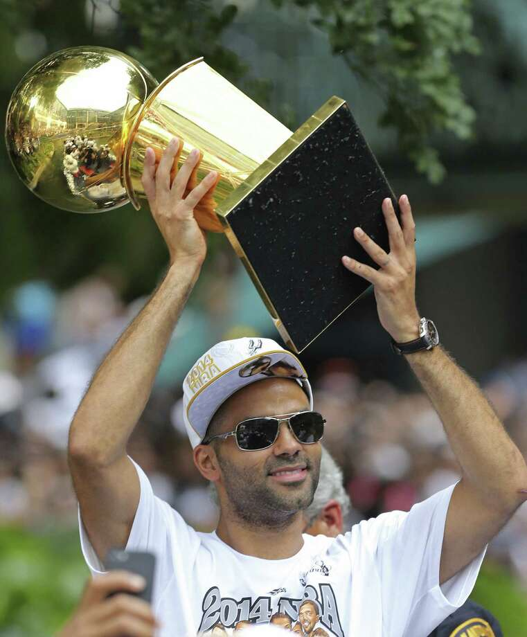 Point guard Tony Parker hoists the O'Brien Trophy aloft for onlookers lining the river to see. Photo: San Antonio Express-News / © 2014 San Antonio Express-News