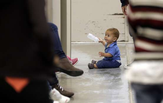 A toddler sits on the floor with other detainees at a U.S. Customs and Border Protection processing facility, Wednesday, June 18, 2014, in Brownsville,Texas. CPB provided media tours Wednesday of two locations in Brownsville and Nogales, Ariz. that have been central to processing the more than 47,000 unaccompanied children who have entered the country illegally since Oct. 1.  (AP Photo/Eric Gay, Pool) Photo: Associated Press