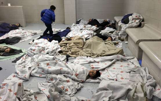 Seen during a media tour, children sleep on the floor of a U.S. Customs and Border Protection center for unaccompanied minors entering the country illegally, in Brownsville, Texas, June 18, 2014. The unprecedented number of children arriving -- many fleeing gang violence in their native countries -- has presented the Obama administration with a humanitarian predicament as well as a political one. (Eric Gay/Pool via The New York Times) -- FOR EDITORIAL USE ONLY. Photo: New York Times