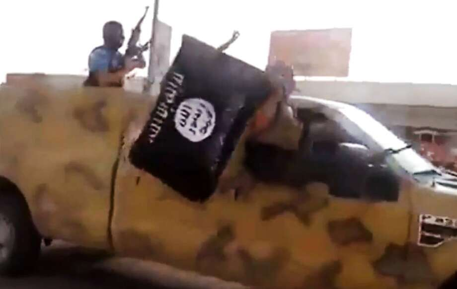 In this Tuesday, June 17, 2014 image taken from video uploaded to a militant social media account, which has been authenticated based on its contents and other AP reporting, al-Qaida-inspired Islamic State of Iraq and the Levant militants arrive to the country's largest oil refinery in Beiji, some 250 kilometers (155 miles) north of the capital, Baghdad, Iraq. Iraqi security forces battled insurgents targeting the country's main oil refinery and said they regained partial control of a city near the Syrian border Wednesday, trying to blunt a weeklong offensive by Sunni militants who diplomats fear may have also seized some 100 foreign workers. (AP Photo via militant video) Photo: ASSOCIATED PRESS