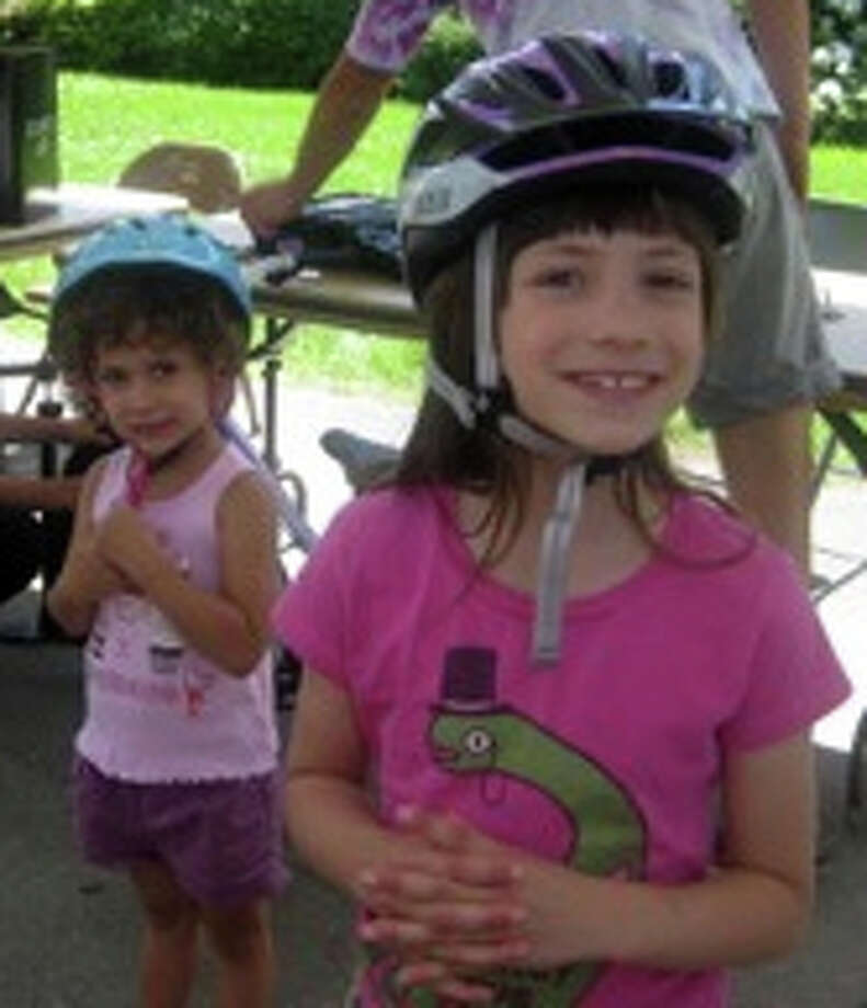 Julia Pierson, 6, and her sister, Siena, 3, get ready to ride at the North Street School bike rodeo on June 7.