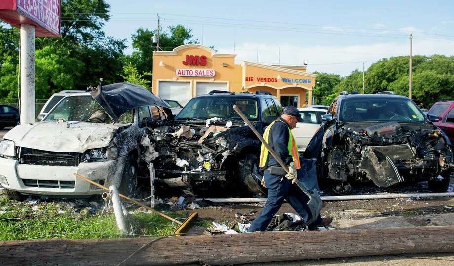 A crew cleans debris after a driver crashed into a row of used cars along Spencer Highway near 4th Street, Thursday, June 19, 2014, in South Houston. Police said the man lost control of his car, veered from the road and slammed into the cars at the auto dealership. At least seven vehicles were damaged. Photo: Cody Duty, Houston Chronicle / © 2014 Houston Chronicle